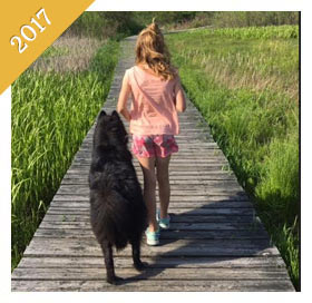 Same child is now a preteen walking same dog on boardwalk from 2017