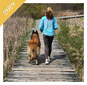 Same preteen walking same dog on boardwalk from 2019