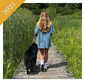 Same teenager is walking same dog on boardwalk from 2021